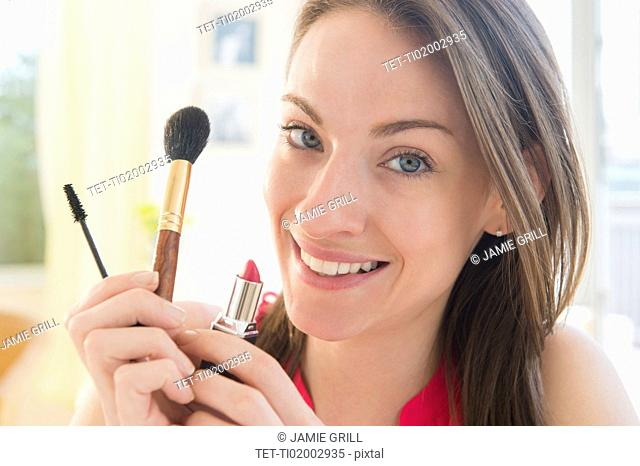 Portrait of woman with make up utensils
