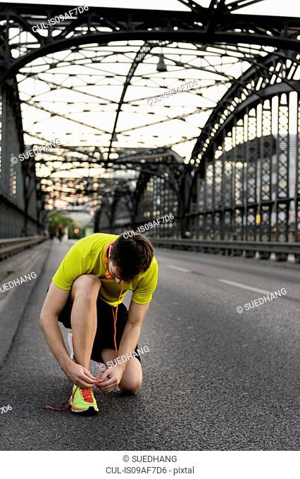 Young male runner kneeling and tying shoelace on bridge