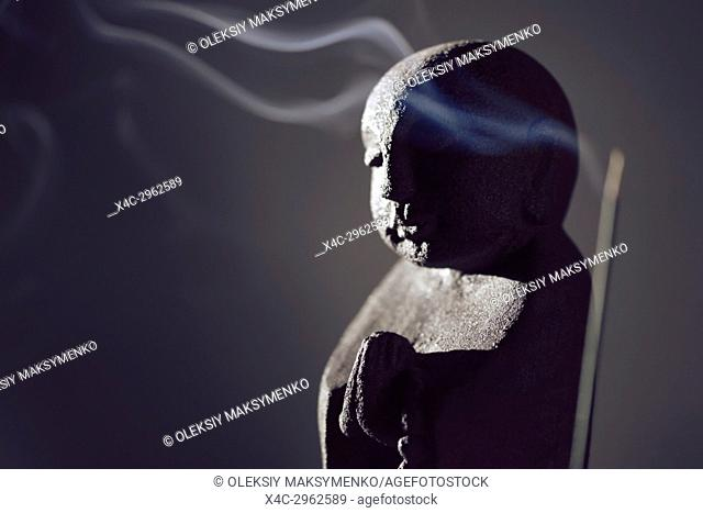 Praying Buddha statue with burning incense smoke in dramatic dim light on dark gray background