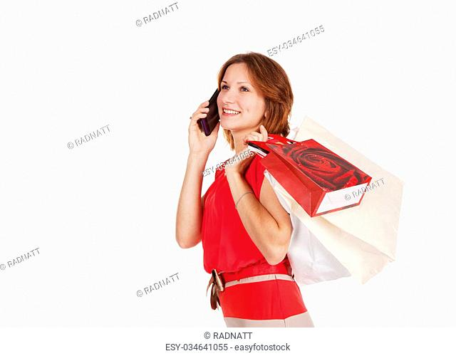pretty girl in red dress with shopping bags calling by mobile