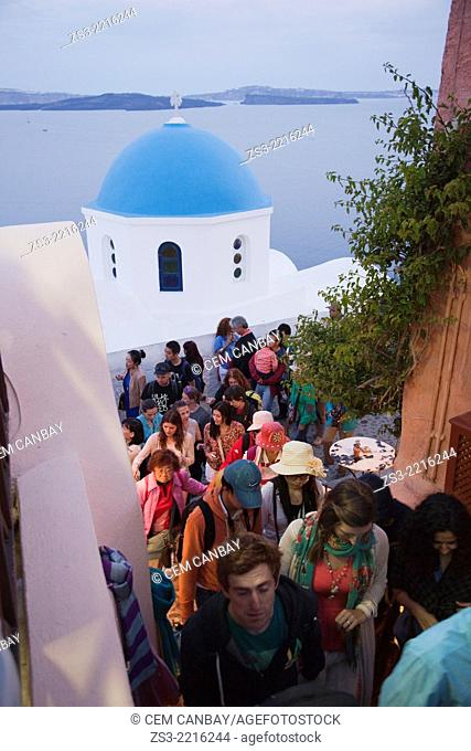 People walking through the alleys of Oia town after sunset, Santorini, Cycldes Islands, Greek Islands, Greece, Europe