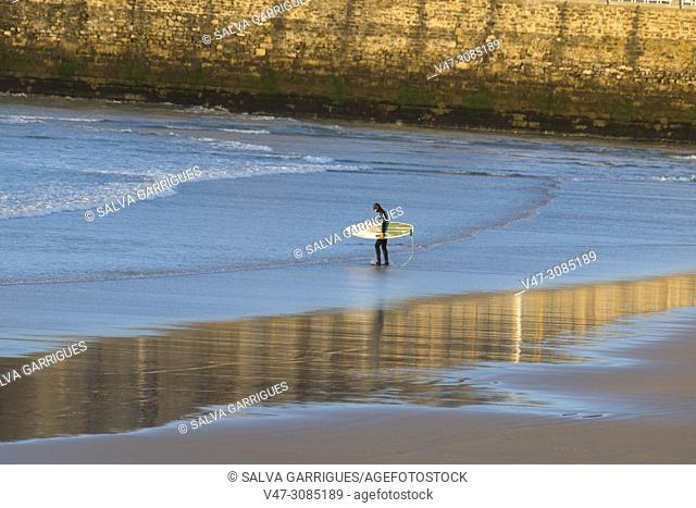 A surfer with neoprene and surfboard enters the sea at La Concha Beach in San Sebastian, Donostia, Guipúzcoa, Spain