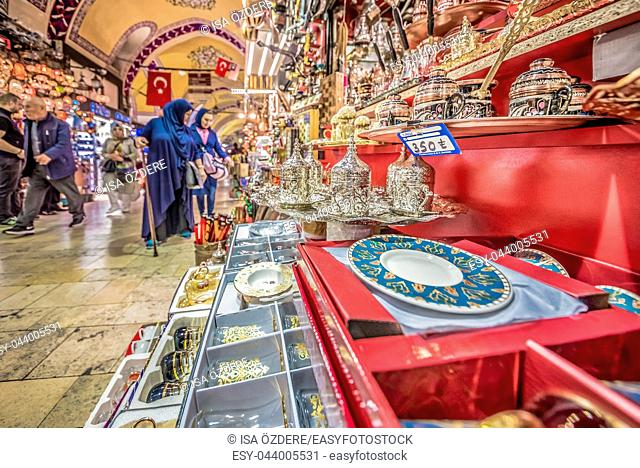 Unidentified Tourists visiting and shopping in the Grand Bazaar in Istanbul. Interior of the Grand Bazaar with souvenirs on the foreground