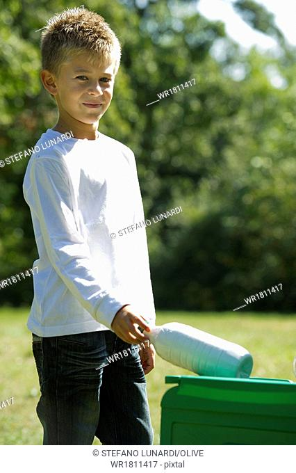 Young boy recycling plastic bottle