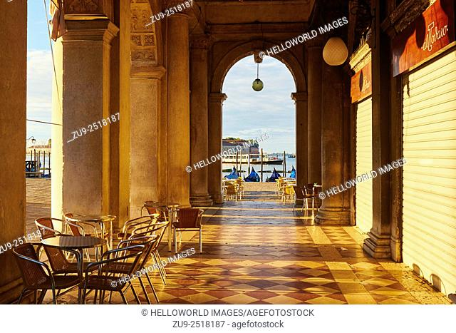 Early morning sunlight on a colonadded passageway looking out towards the Venetian Lagoon, St Mark's Square, Venice, Veneto, Italy, Europe