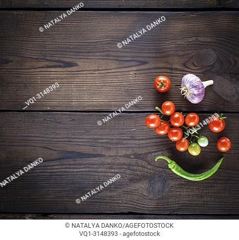 fresh ripe red cherry tomatoes, garlic and green chile peppers on a brown wooden background, empty space on the left, top view
