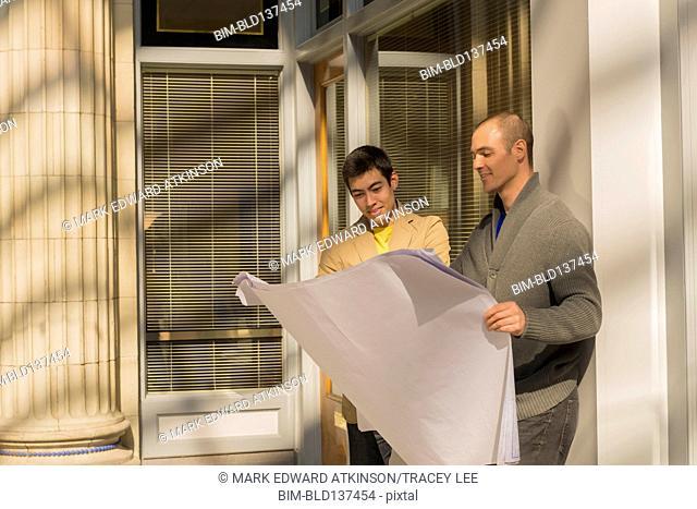 Men reading blueprints outdoors