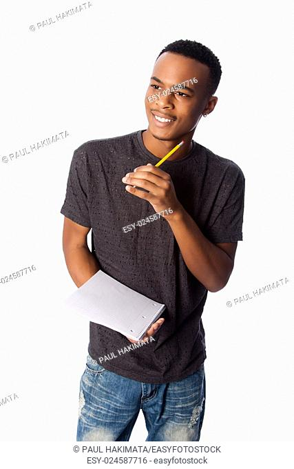 Handsome happy student standing thinking with pencil and notepad coming up with ideas, on white