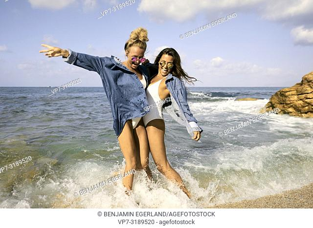 Two women jumping in sea water at beach, Chersonissos, Crete, Greece