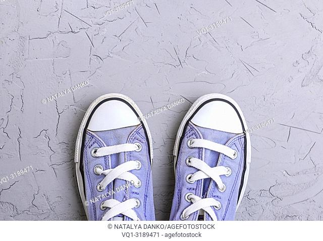 pair of old worn purple sneakers with white laces on a gray background, top view