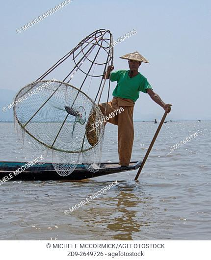 A fisherman poses for tourists on Inle Lake