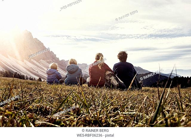 Italy, South Tyrol, Geissler group, family hiking, sitting on meadow