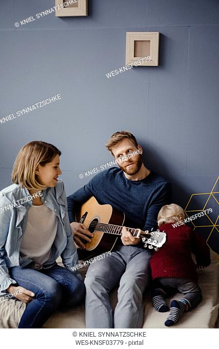 Happy family playing music with their son at home