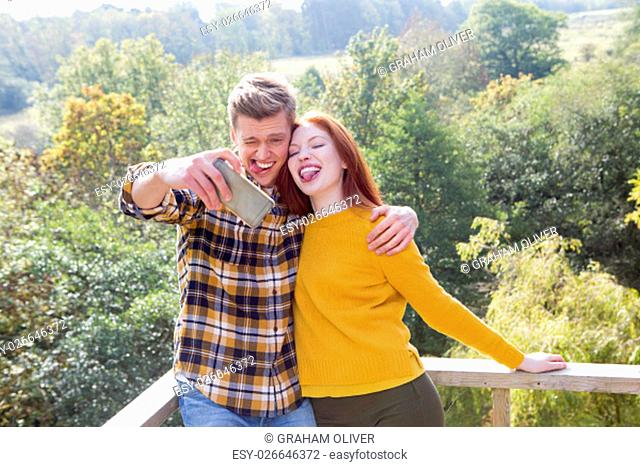 Young couple taking a silly selfie on their garden balcony, using a smart phone