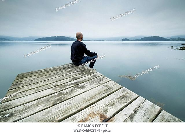 Lonely man sitting on jetty looking at distance