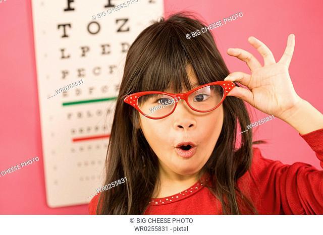 Girl wearing eyeglasses in front of eye chart
