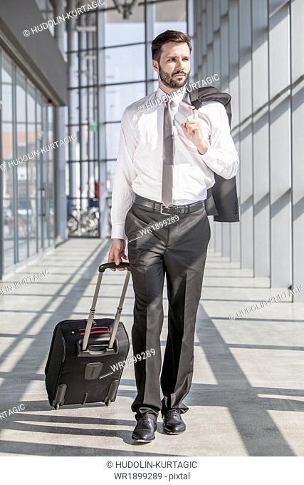 Businessman pulling luggage in modern lobby