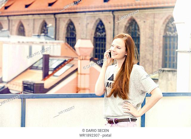 Young woman using smart phone on balcony, Munich, Bavaria, Germany