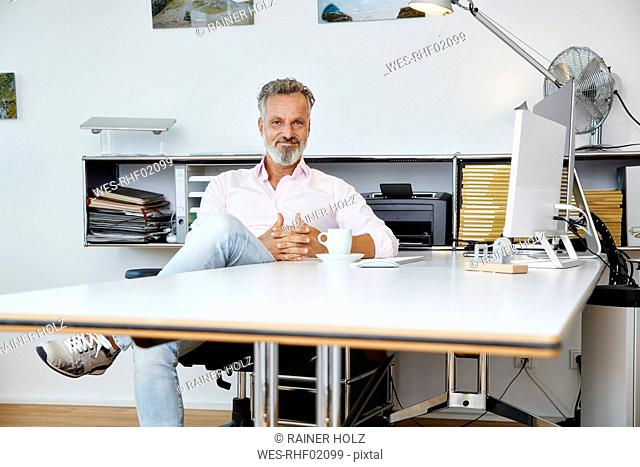 Portrait of confident businessman sitting at desk in office