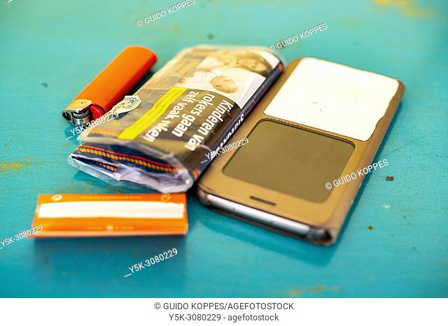 Tilburg, Netherlands. Smartphone, Tabacco and Lighter, owned by an attractive redheaded woman, left behind om on a dining room table