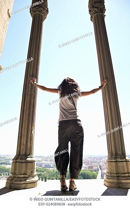 woman back looking at horizon between columns of cloister inside old cathedral of Lleida city in Catalonia Spain Europe