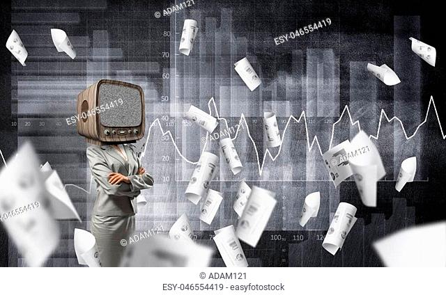 Business woman in suit with old TV instead of head keeping arms crossed while standing against flying papers and analytical charts drawn on dark wall on...