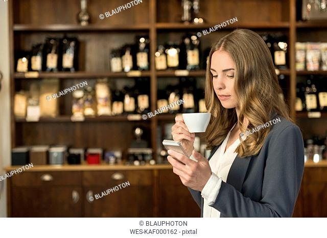 Young woman drinking coffee in a coffee shop looking at her smartphone