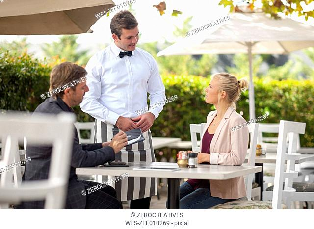 Waiter and couple at outdoor restaraunt