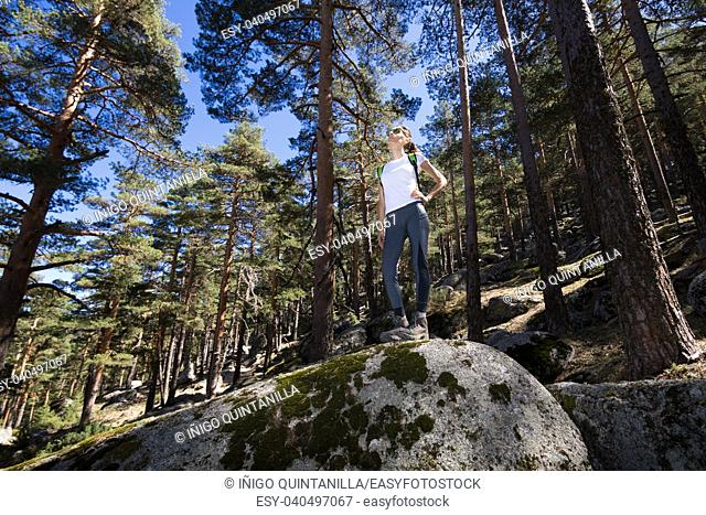view from below of sport hiker woman with white shirt grey trousers standing posing on a great rock in the forest in Navacerrada mountain