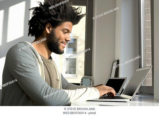 Man working in front of window at home with laptop