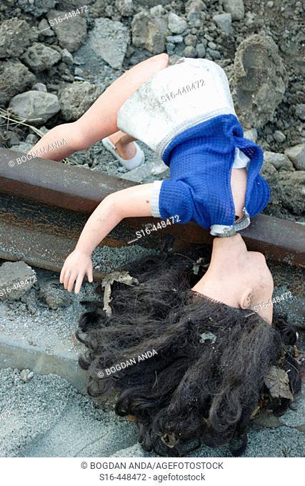 Broken doll thrown on a rail track