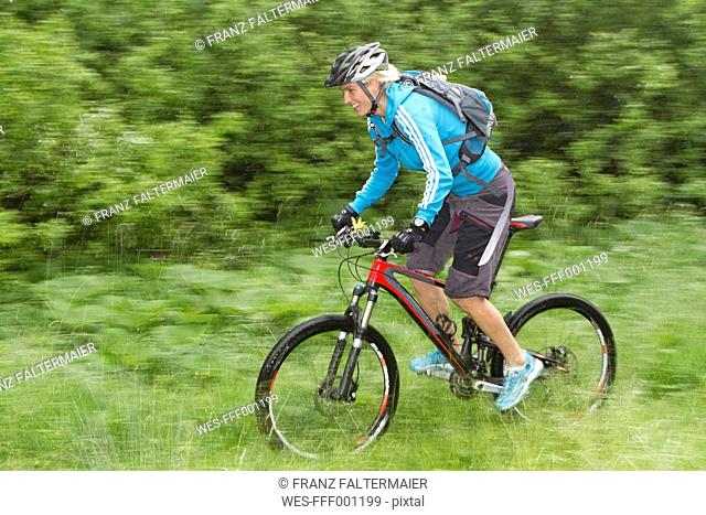 Germany, Bavaria, Schliersee, Mid adult woman moutainbiking in rain