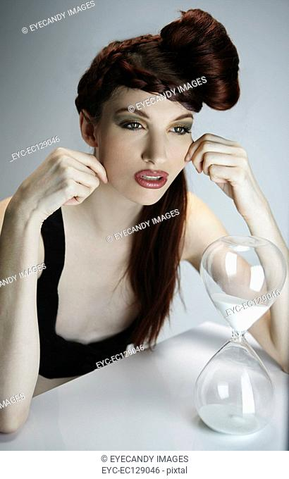 Portrait of stylish woman with retro hairstyle sitting with hourglass ticking away, studio shot