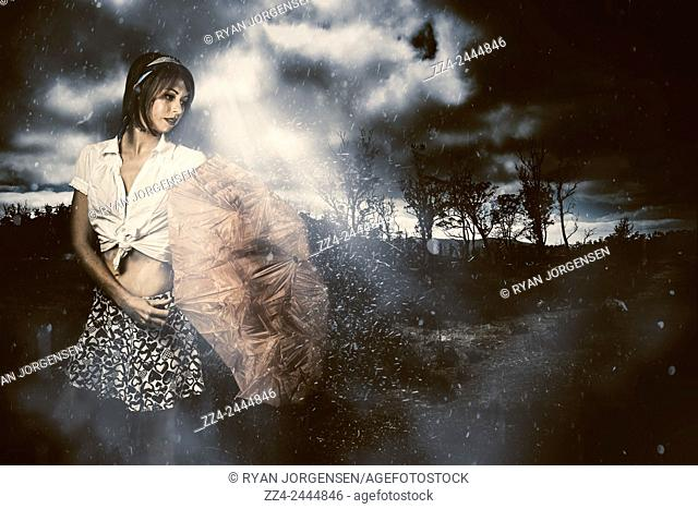 Dark dramatic fine artwork of a woman standing in a dark field shaking off rain from a passing storm beneath a beam of luminous light