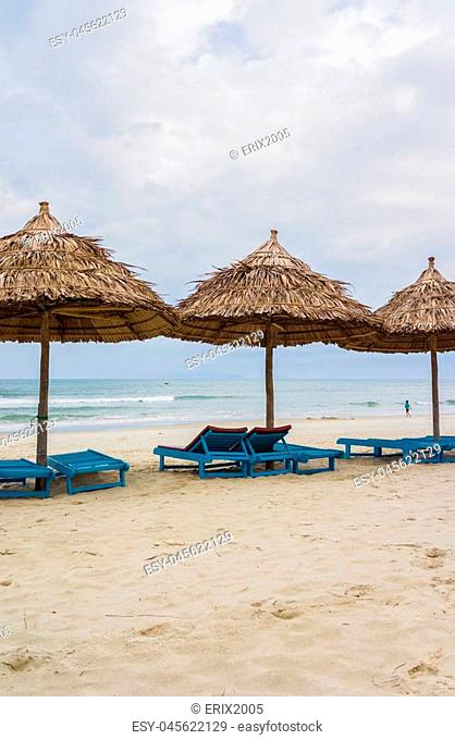 Shelter of palm leaves and sunbeds in the China Beach in Da Nang, Vietnam. It is also called Non Nuoc Beach. South China Sea on the background