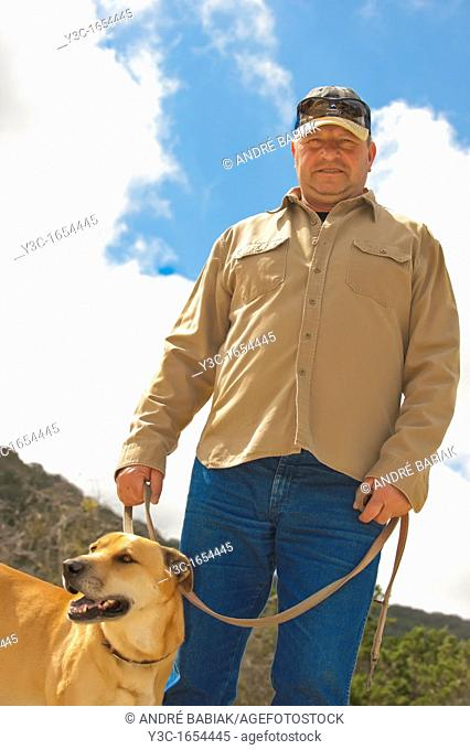 Middle aged man taking his dog on the leash for a walk