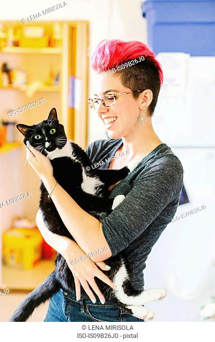 Young woman with pink carrying wide-eyed cat in kitchen