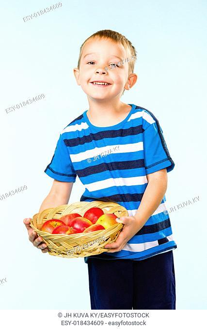 Little boy on striped t-shirt, fruit basket, studio shot and light blue background