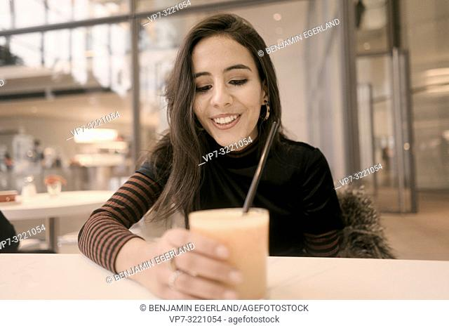 portrait of happy woman holding healthy juice glass while enjoying break at table in café, in Munich, Germany