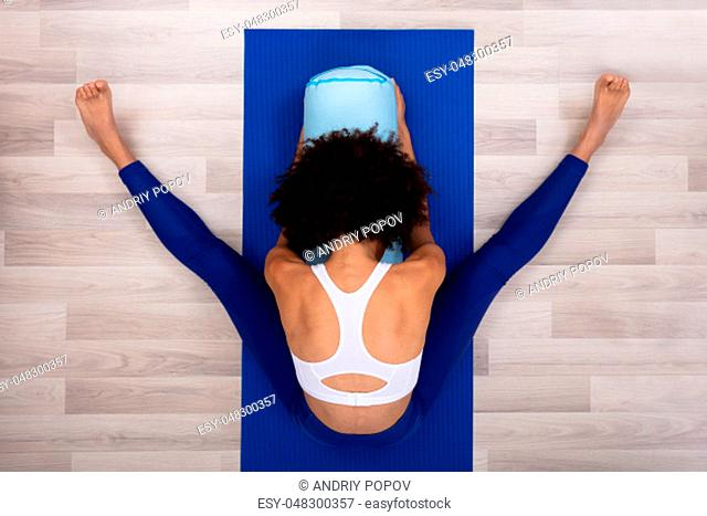 An Overhead View Of A Young Woman Sitting On Blue Exercise Mat Doing Yoga