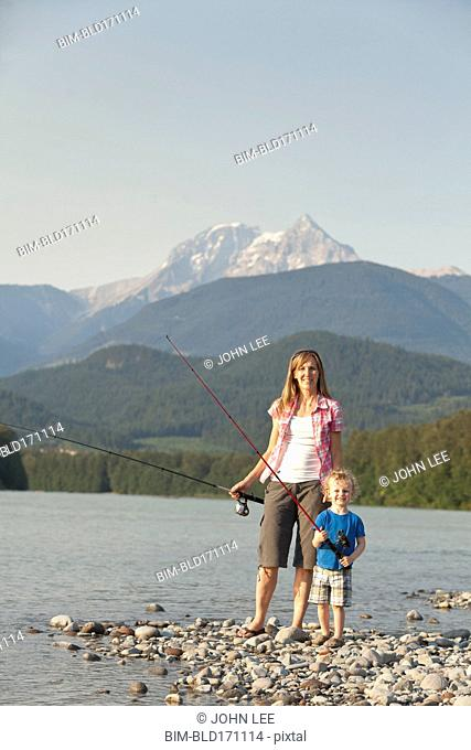 Caucasian mother and son fishing in remote lake