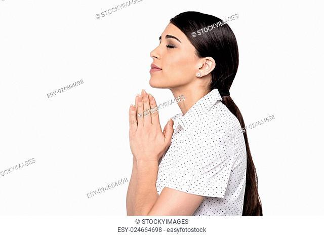 Side pose of young woman praying