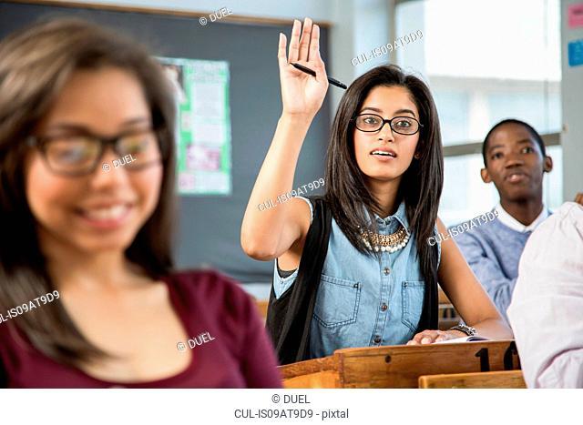 Female student in classroom, hand raised