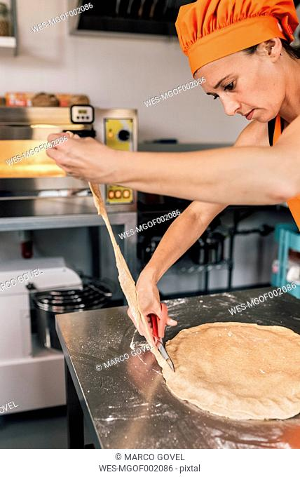 Woman preparing pizza dough