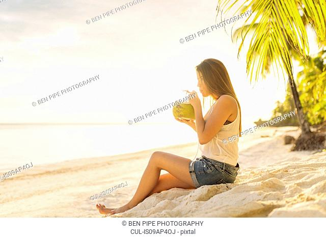 Young woman drinking fresh coconut milk on Anda beach, Bohol Province, Philippines