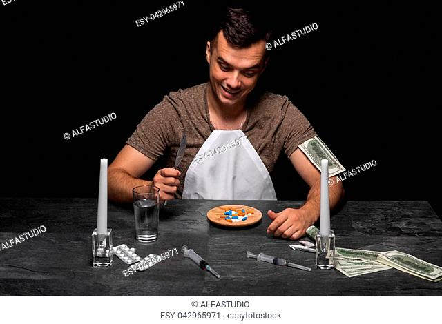 Drug-dependent teenager sitting at the table. A guy with a drug addiction on a black background. A young man in a T-shirt and a white bib eating drugs from a...