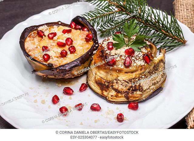 Plate with eggplant zuccotto decorated for Christmas with pomegranate seeds and fir branch