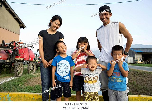 Portrait of smiling Japanese farmer, his wife and four children standing in their yard, children pulling faces at camera