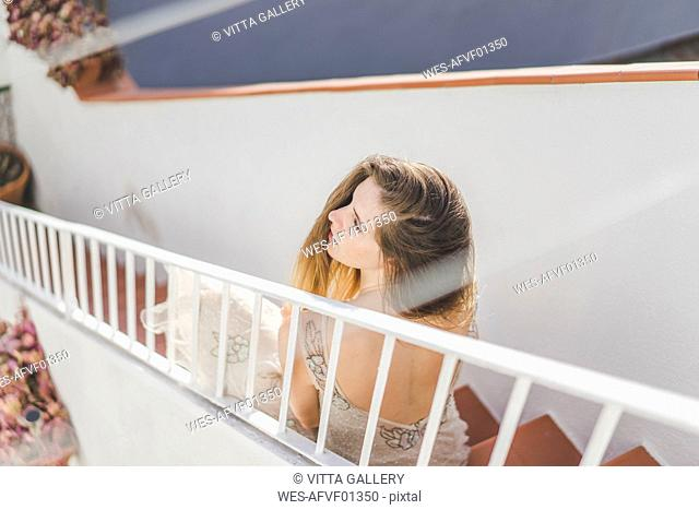 Young woman wearing a wedding dress, sitting on stairs