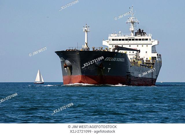 Detroit, Michigan - A sailboat near the Edzard Schulte, a British oil/chemical tanker sailing at the southern end of Lake St. Clair